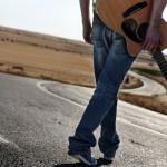 Mann mit Jeans und Gitarre auf der Strasse