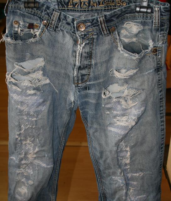 Löcherige Jeans vor der Reparatur.